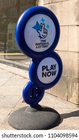 A National Lottery sign on the pavement outside a newsagents shop in Warrington Cheshire inviting people to come in and play May 2018