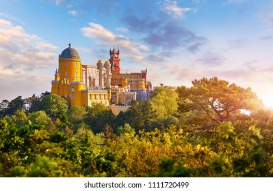 National Palace of Pena in Sintra, near Lisbon, Portugal. Picturesque landscape with dawn and green trees. Blue morning sky with clouds.
