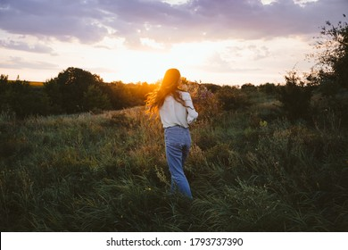 National Relaxation Day, relaxation practices, mental health, slow living concept. Young girl with long windy hair and flower bouquet enjoying nature on the background of sunset.