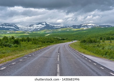 National road 95 in Sweden in approach of Norwegian frontier Merkenisvuopmekietje. Tundra forest valleys and Scandinavian mountains partially hided with clouds are at background.