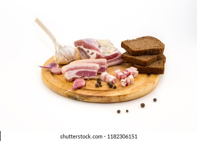 National Russian and Ukrainian food is salo. Sliced bacon on a wooden board. On a white background.