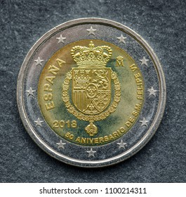 National side of two euro coin issued by Spain isolated on a black background. Special Edition 50th Anniversary of King Felipe VI, represented by his coat of arms