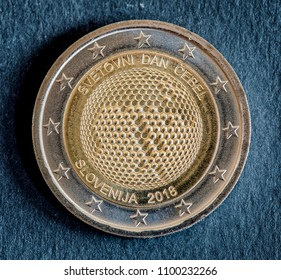 National side of two euro coin issued by Slovenia isolated on a black background. Special edition of 2018 World Bee Day