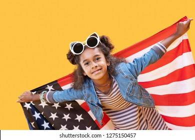National symbol. Positive cheerful girl standing with a US flag while smiling to you