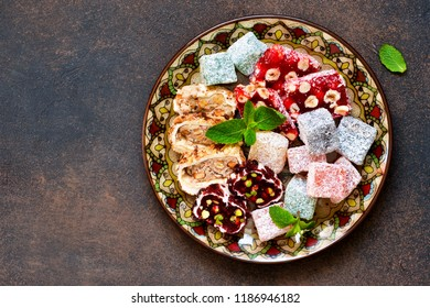 National Turkish dessert. Plate with various pieces of turkish delight lokum on a dark concrete background.
