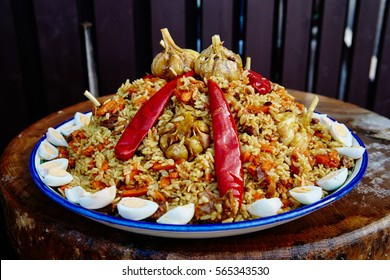 National Uzbek dish pilaf. Cooking in a cauldron on fire. Spread beautifully on a national plate lyagan rice, from above slices of the cut meat and decorate with red pepper and garlic