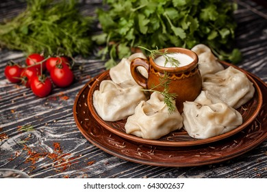 National Uzbek Dishes manti on clay plates, hot red pepper, ayran, parsley, spices are lying on a wooden table