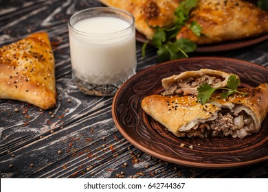 National Uzbek samsa dishes in clay dishes with ayran on a wooden table