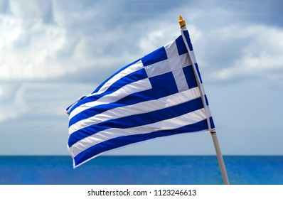 National waving Greek flag and mediterranean sea. Blue sky and Greece flag as background aegean sea. Greece flag is flying.