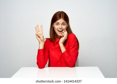 A national woman in a red shirt sits at a table and shows fingers on her hand