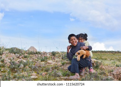 Native american boy holding his little sister in the countryside.