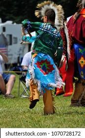 A Native American boy in traditional regalia participates in a group dance.