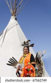 A Native American in ceremonial costume and teepee.