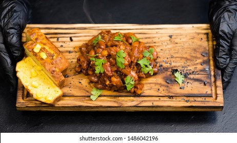 Native American cuisine. Boston baked beans and cornbread on rustic wooden board in chef hands.