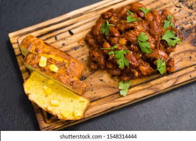 Native American cuisine. Top view of Boston baked beans and cornbread on rustic wooden board.