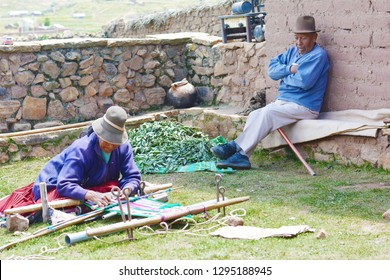 Native american family in the countryside. Old woman weaving and old man speaking to her.