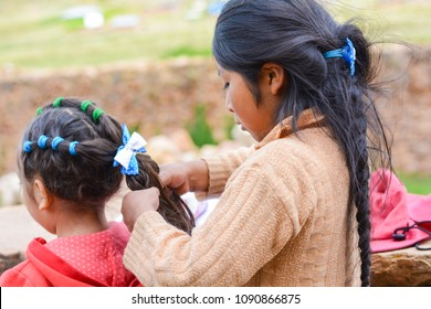 Native american girl doing braid for her little sister.