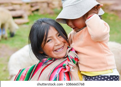Native american girl with typical aymara cloth holding her little sister outside.