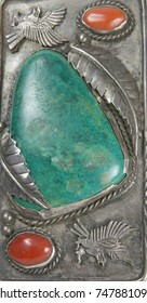 Native American handmade turquoise and red stones set in a leaf pattern of gray metal in a belt buckle