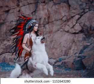 Native American Indian hunts. The wolf attacks in a jump. A luxurious roach with very long feathers. The Husky Dog. Beads on the chest. Art photo.