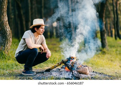Native american indian peruvian indigenous man in straw hat sitting in forest outdoor in summer above bonfire with smoke and torch at hand. Shaman rite. Spiritual ceremony. Young sorcerer.