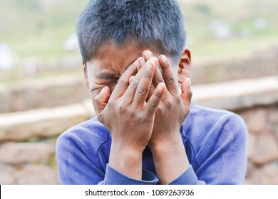 Native american kid crying and closing his face with hands.