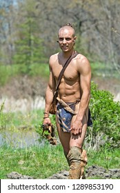 native American male warrior wearing a loin cloth and carrying a rifle and knife