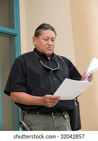 Native American man stepping out of an office building and reading papers.