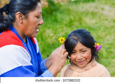 Native american mom decorating hair of her little daughter with flowers.