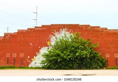 Native American mural on a brick wall behind a tree in Tulsa Oklahoma circa May 2010