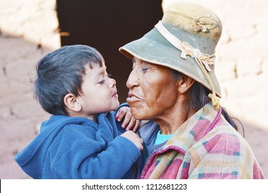 Native american old woman holding her little grandson. Happy interracial family.