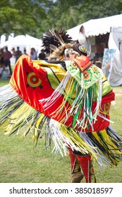 Native American performers dancing at a pow-wow dressed in their traditional costumes representing their tribes.