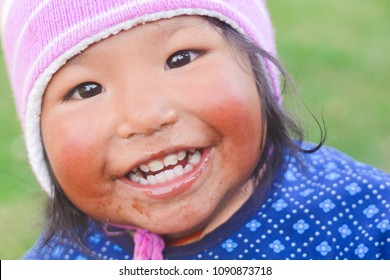 Native american toddler girl with pink hat smiling outside.