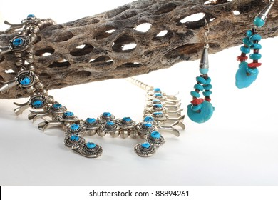 Native American turquoise squash blossom necklace and earrings displayed on z dried stick of cholla cactus against neutral background.  Made by Navajo Nation silversmith.