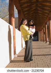 Native American woman & daughter in afternoon sun under a canopied walkway