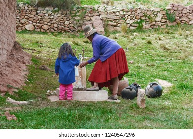 Native american woman with her little daughter using water from the faucet.