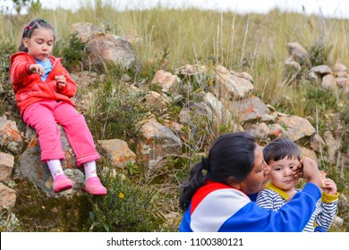 Native american woman with her two children in the countryside. Mom comforting her son. The daughter is jealous.
