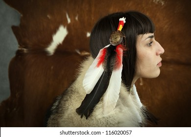 Native american woman profile  portrait. Young beautiful woman in native american costume with wolf fur feather head decoration