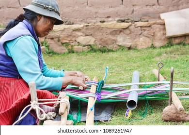 Native american woman weaving typical aymara clothing.