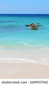 Native Dominican Republic island wooden fishing boat full of nets and floats with oars left at anchor off sandy shores and sea foam surf with Caribbean blue water background and copy space.