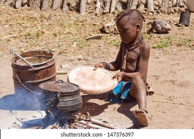 Native Himba boy cooking lunch, Namibia