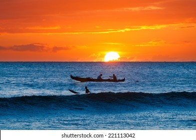 A native outrigger boat and lone surfer in silhouette waiting for a wave at sunset on Maui, Hawaii, USA