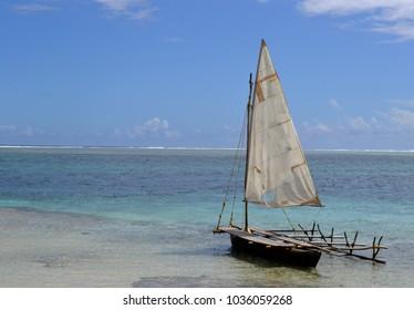 Native outrigger canoe with sail on deserted beach, Mystery Island, Vanuatu