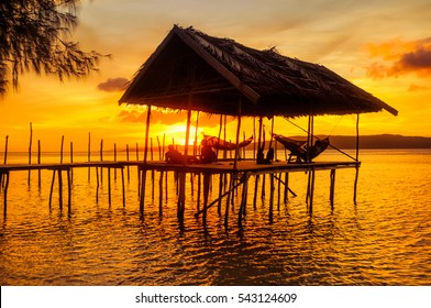 Native people relaxing in hammocks on wooden jetty during sunset on Kri island, Raja Ampat, West Papua, Indonesia.