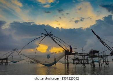 Native southern Thai fisherman catching fish from big square dip net. Traditional style fishery in south of Thailand.