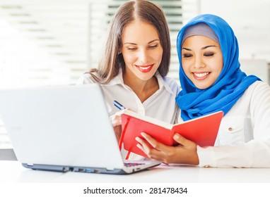 Native speaker teaching a muslim asian girl in a light classroom in college