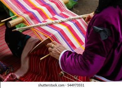 Native woman weaving intricate llama garments using a traditional hand loom.