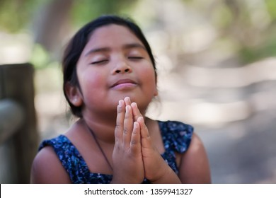 A native young girl with hands together in prayer, in an outdoor setting praying to God with a subtle smile.