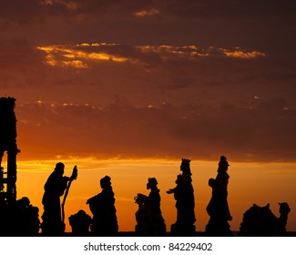 A nativity scene with wise men set against a dramatic sunrise