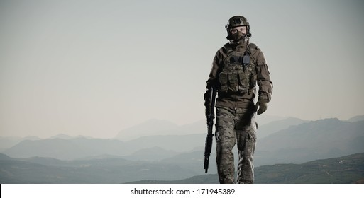 NATO soldier with a rifle. Steps against mountains.